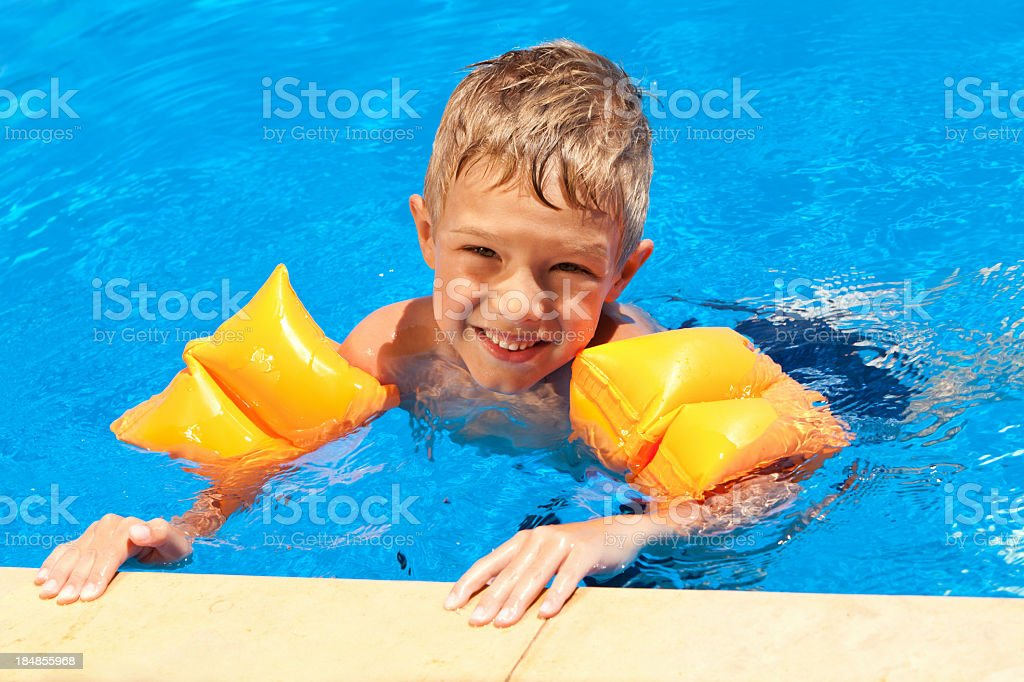 Little Boy With Water Wings Relaxing In The Swimming Pool stock photo