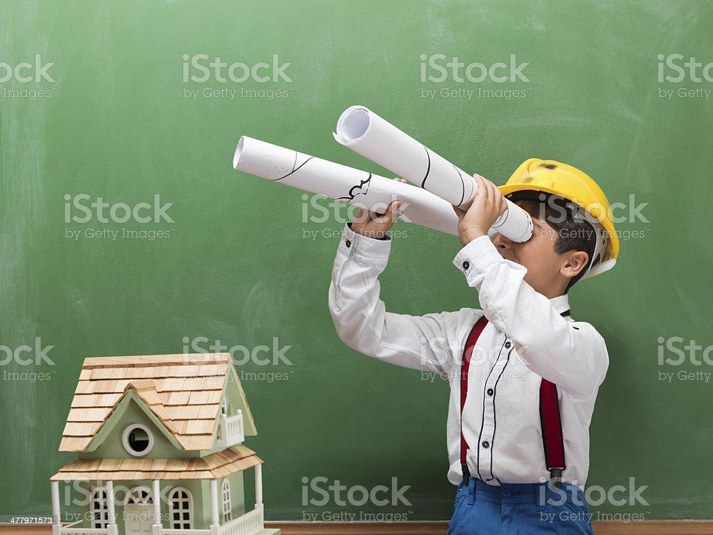 Little boy with yellow hardhat looking through blueprints as binoculars royalty-free stock photo