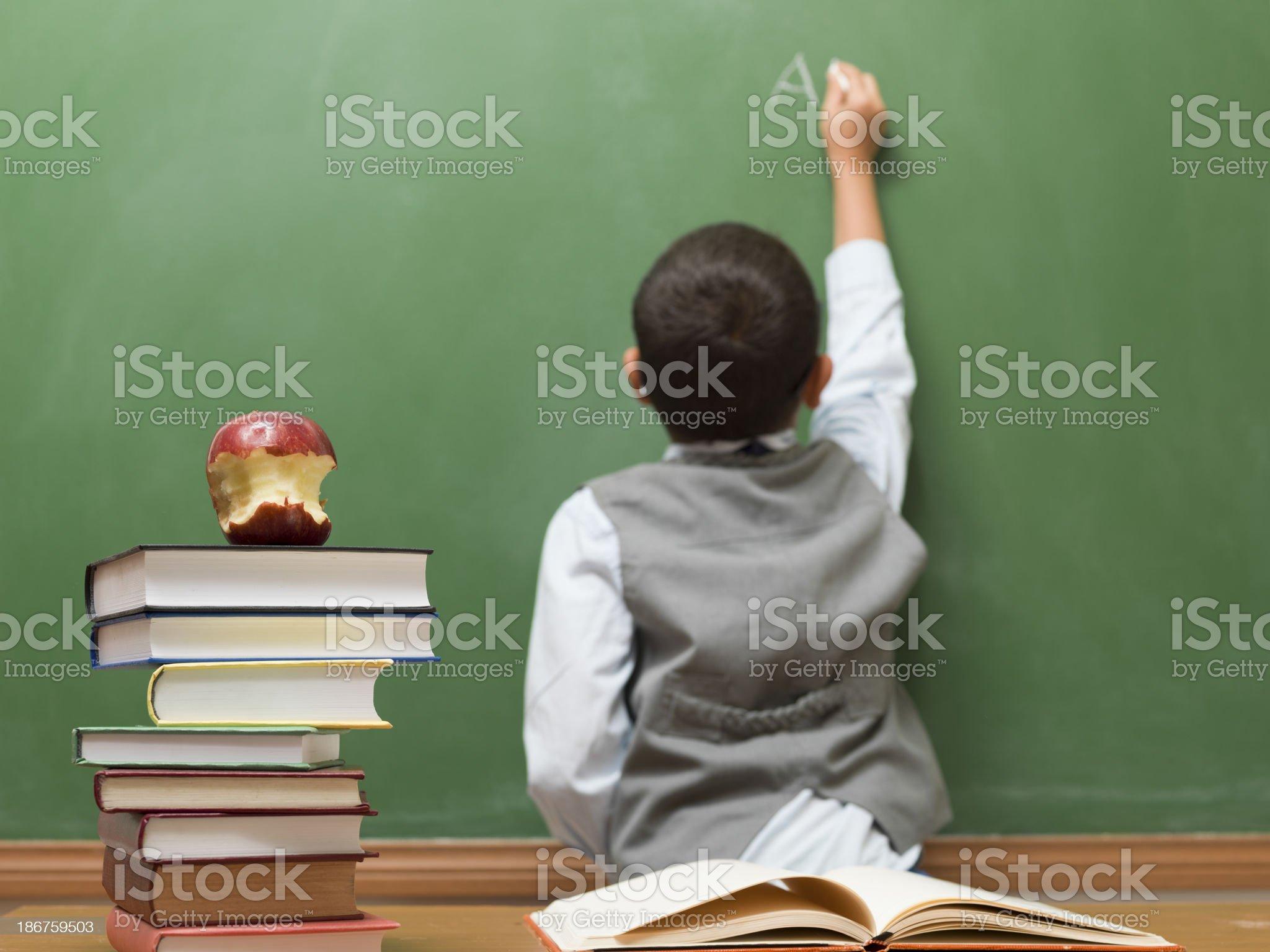 Little boy writing on blank blackboard royalty-free stock photo