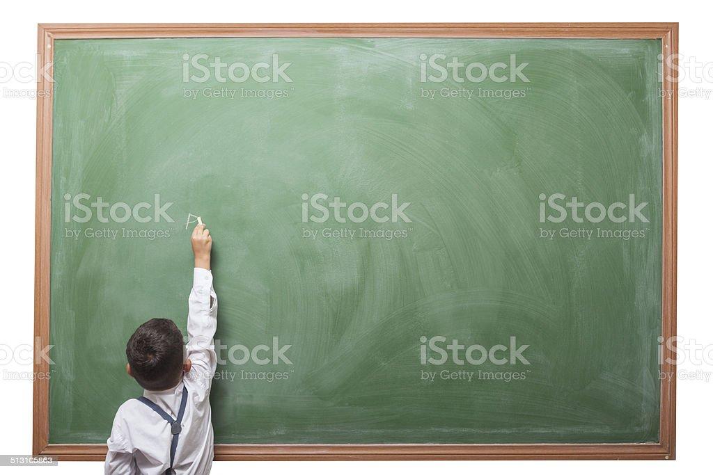 Little boy writing on blank blackboard stock photo