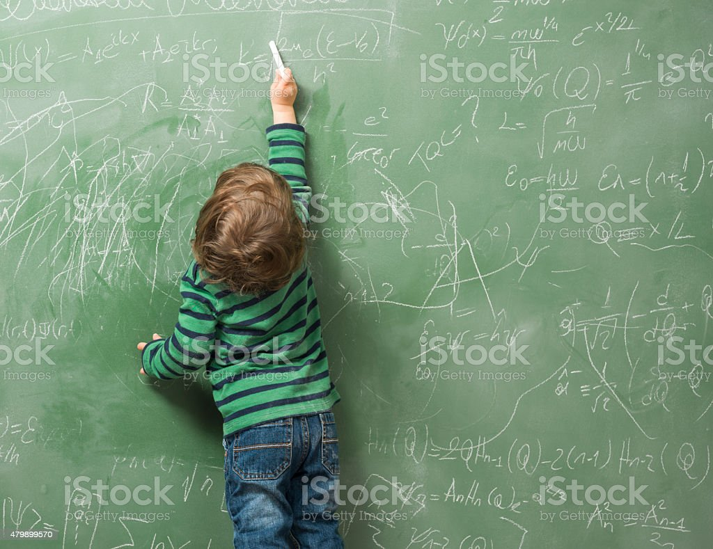 Little boy writing on green blackboard stock photo