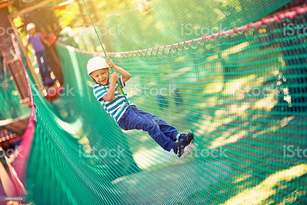 Little boy zipping in adventure park stock photo