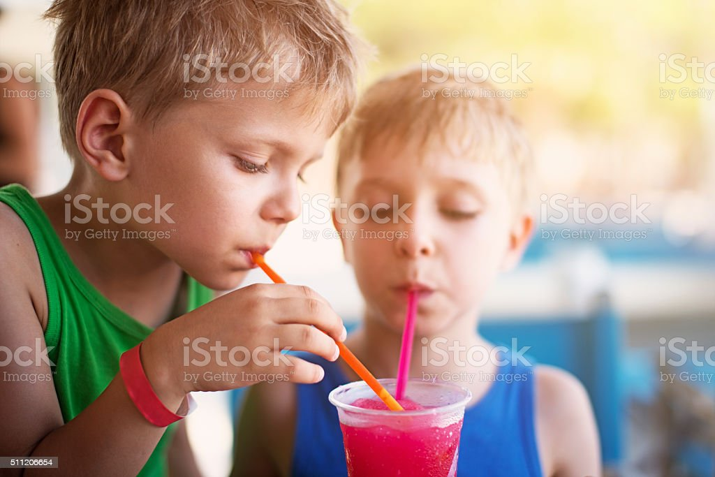 Little boys drinking soda with crushed ice on summer day stock photo