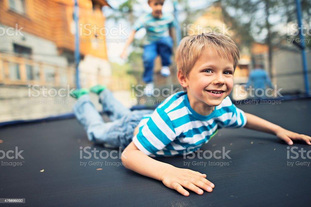 Little boys having fun on garden trampoline stock photo