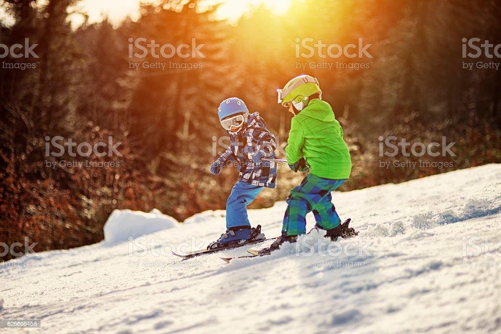 Little boys having fun skiing stock photo