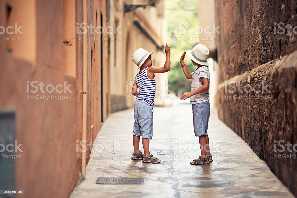 Little boys high five in a narrow street stock photo