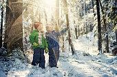 Little boys in winter forest