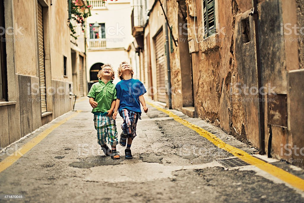 Little boys laughing in a mediterranean street stock photo