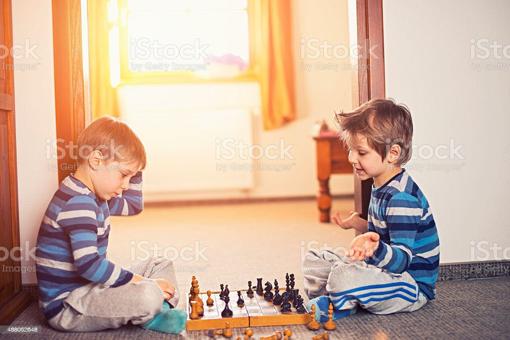 Little boys playing chess together stock photo
