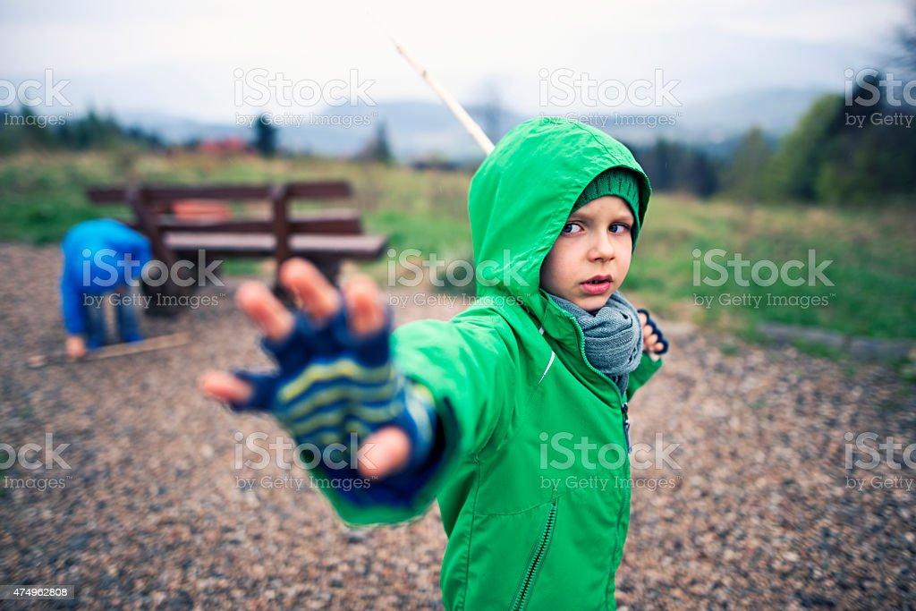 Little boys playing jedi knights stock photo