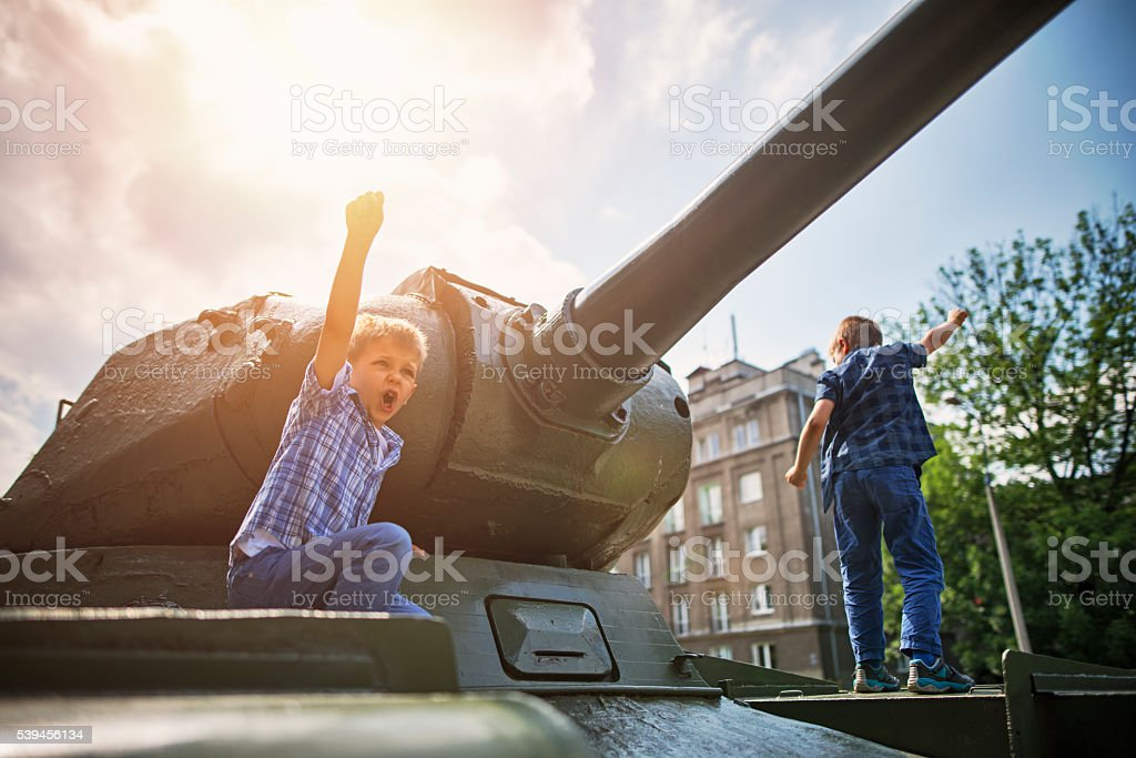 Little boys playing with historical world war 2 tank stock photo