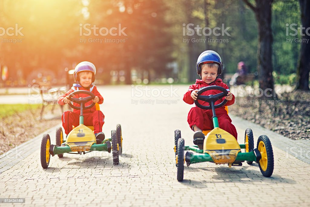 Little boys racing on pedal go-karts stock photo
