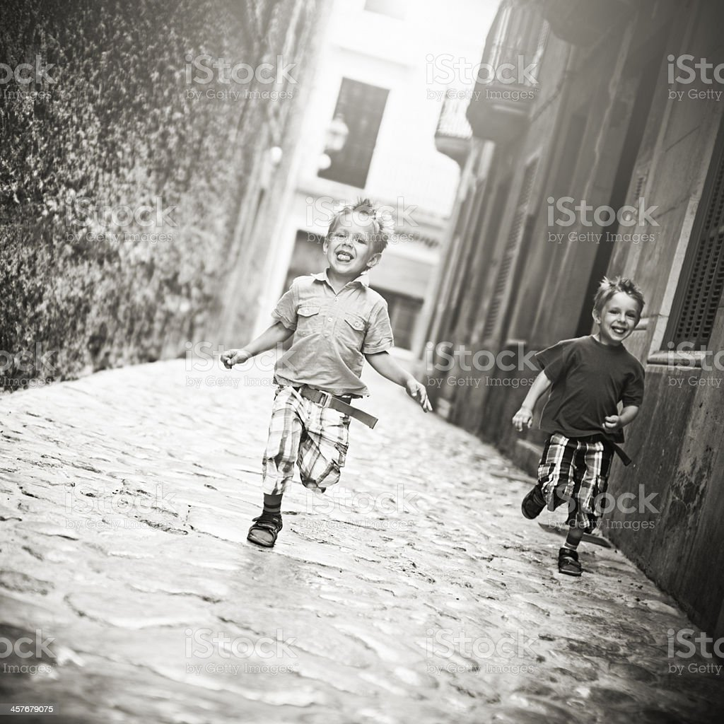 Little boys running in a old town street royalty-free stock photo
