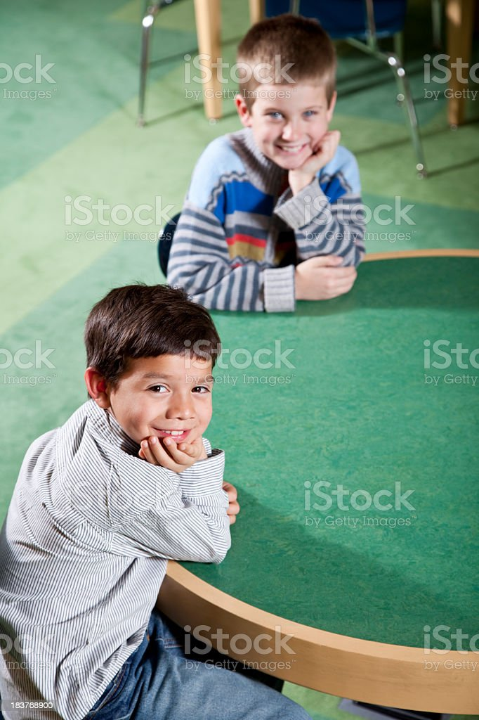 Little boys sitting at round table in school stock photo