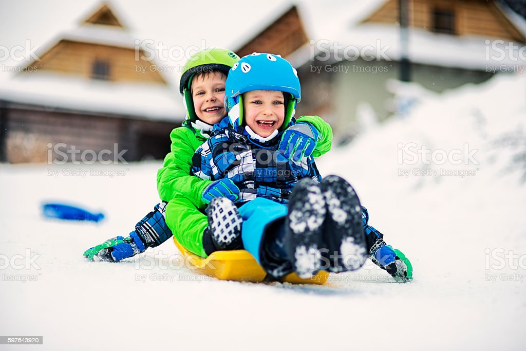 Little boys sliding on sled in winter stock photo