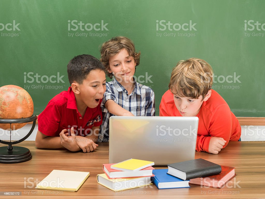 Little boys studying on computer in front of blackboard stock photo