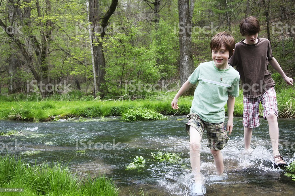 Little Boys Walking Splashing in Stream- Wooded Green Park royalty-free stock photo