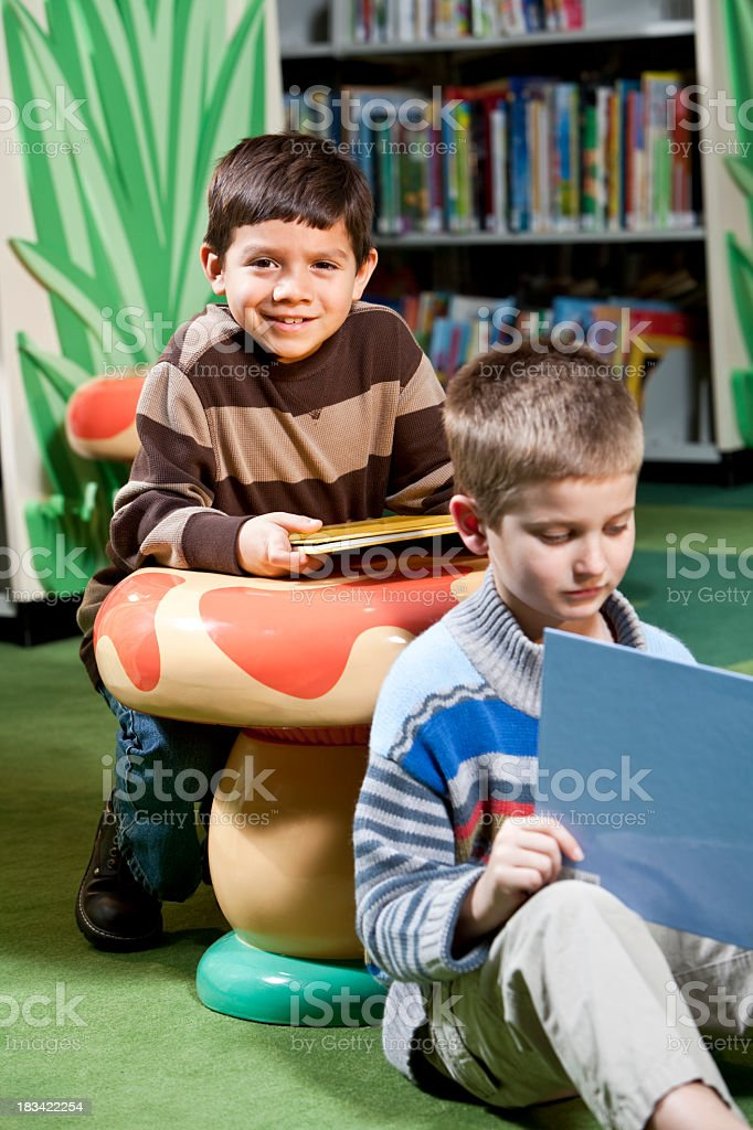 Little boys with books in library stock photo