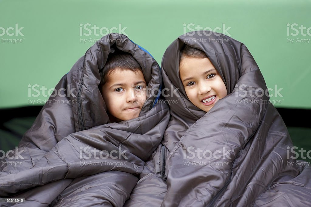 Little brother and sister wrapped in sleeping bag stock photo