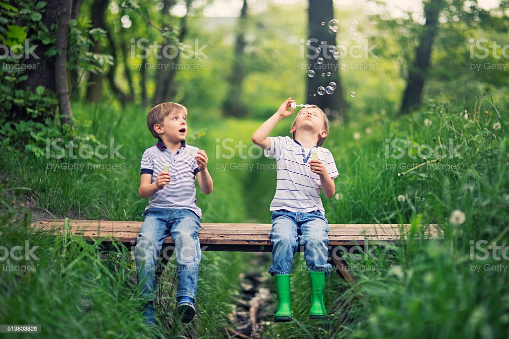 Little brother blowing  bubbles on a little bridge in forest stock photo