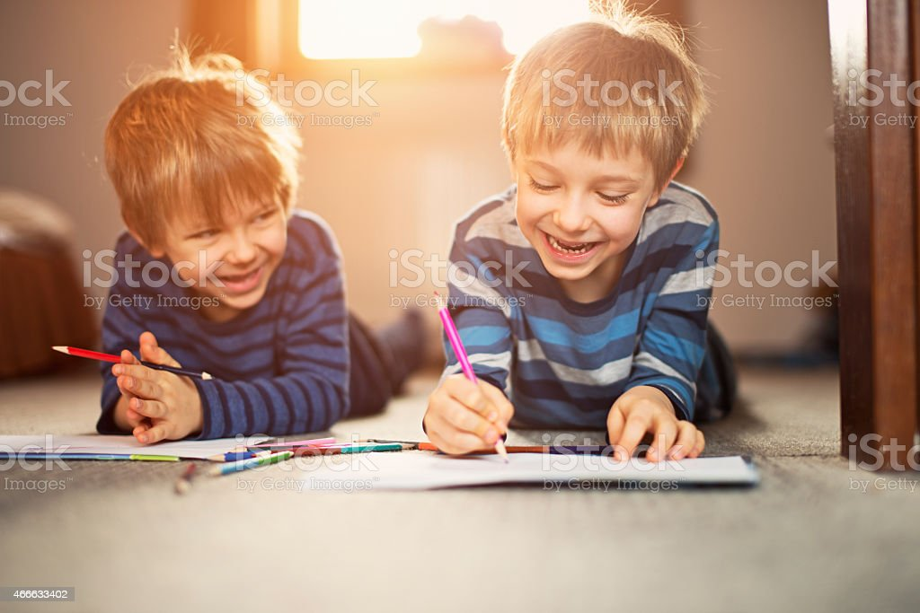 Little brothers enjoying drawing together stock photo