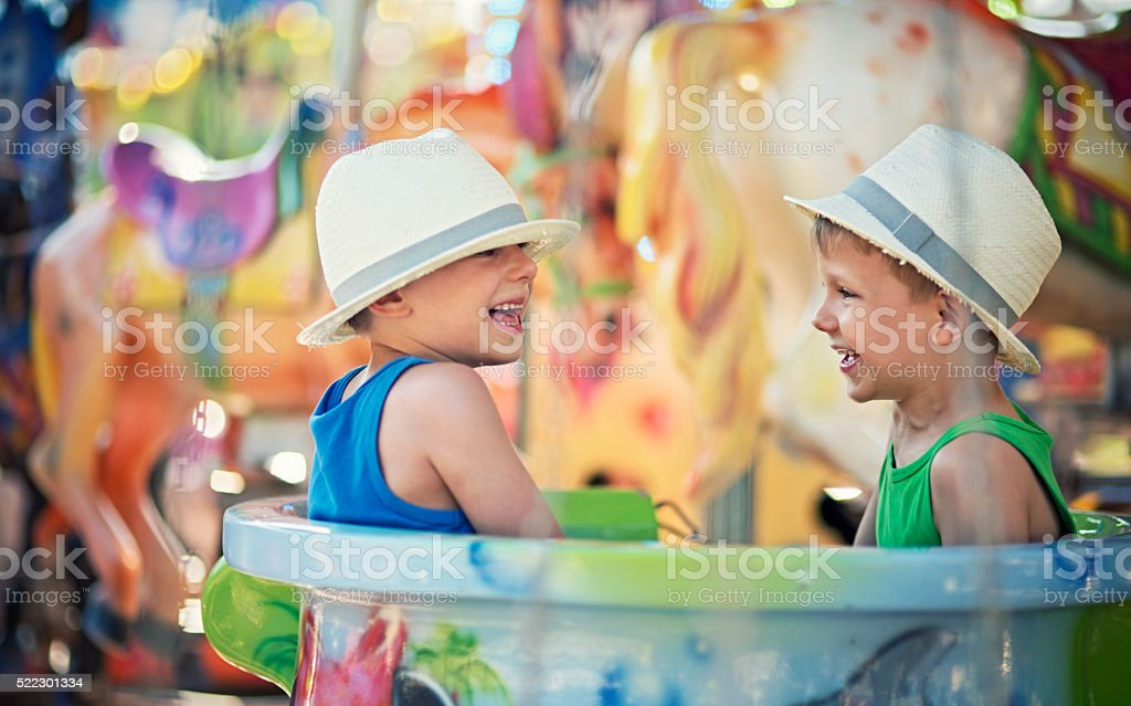 Little brothers having fun on carousel. stock photo