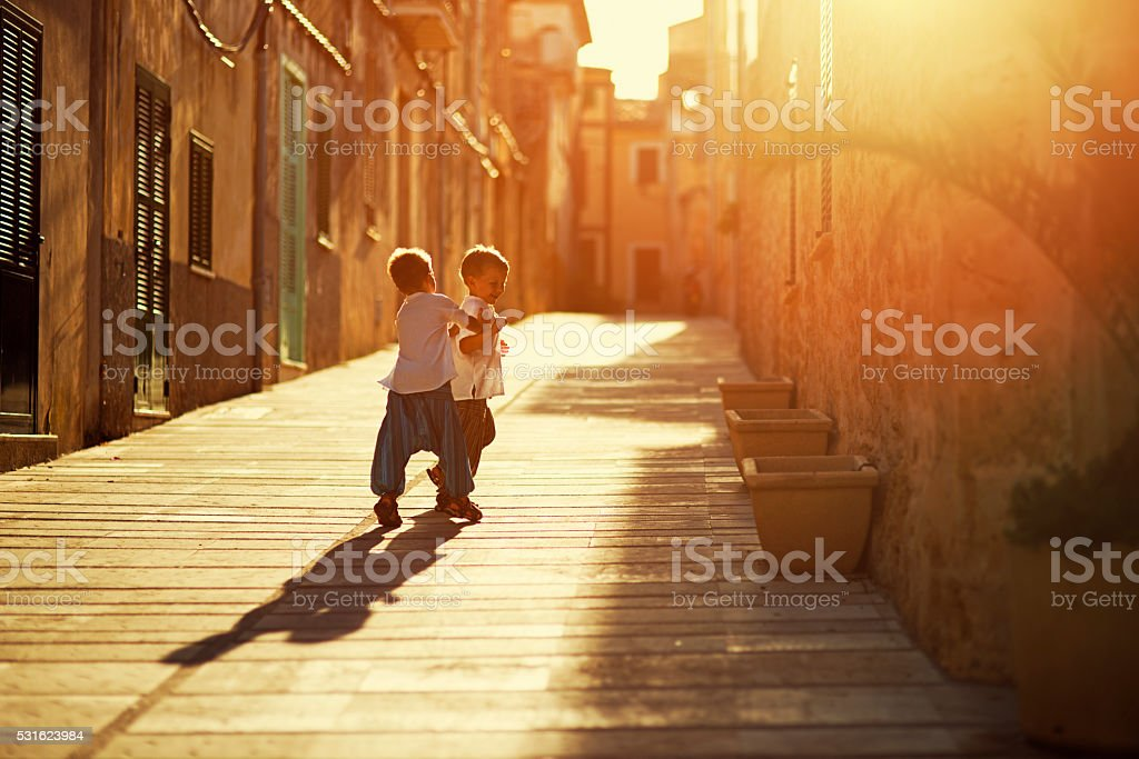Little brothers playing in a  mediterranean street stock photo