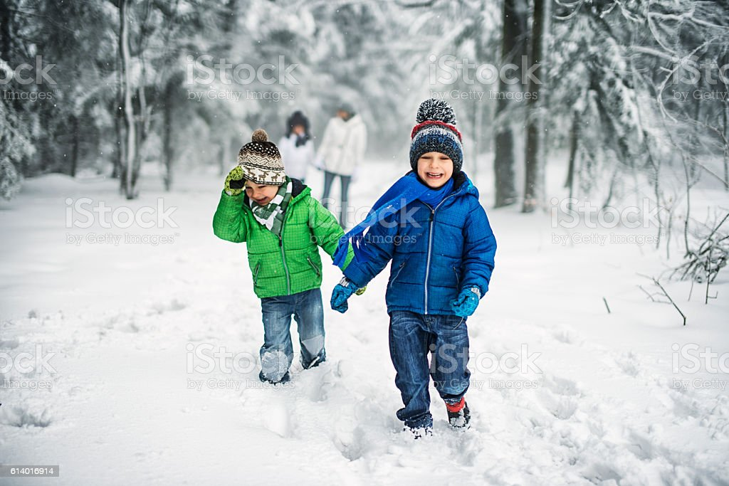 Little brothers with family enjoying winter walk in forest. stock photo