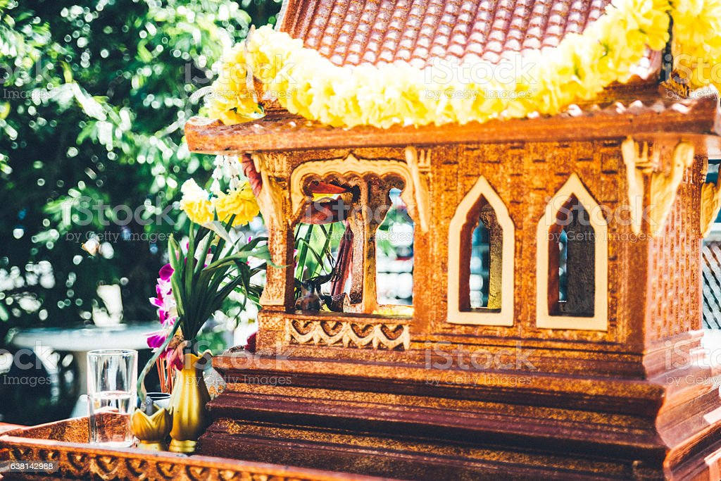 Little buddhist spirit house in Thailand with sacrificial offering stock photo