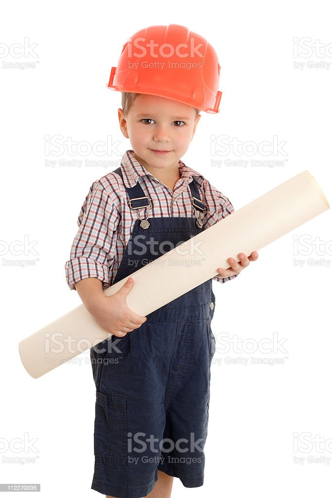 Little builder in coveralls and helmet with blueprint stock photo
