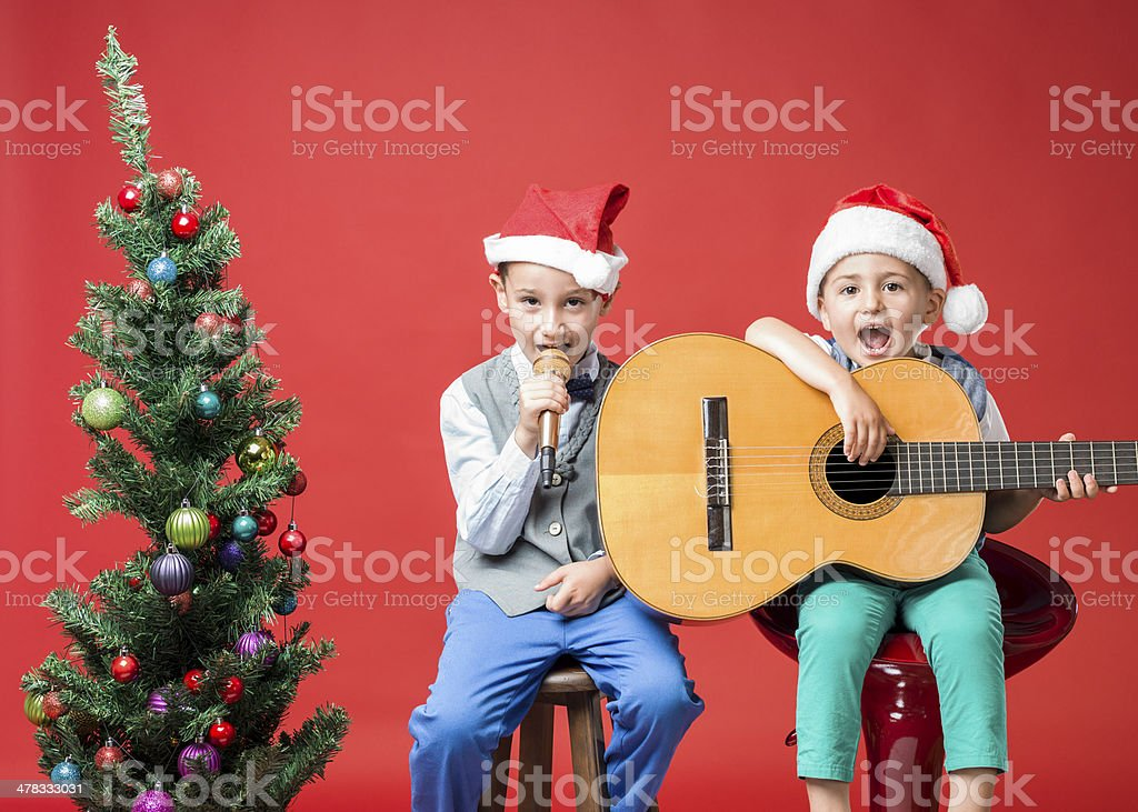 Little carolers making music for Christmas on red background stock photo