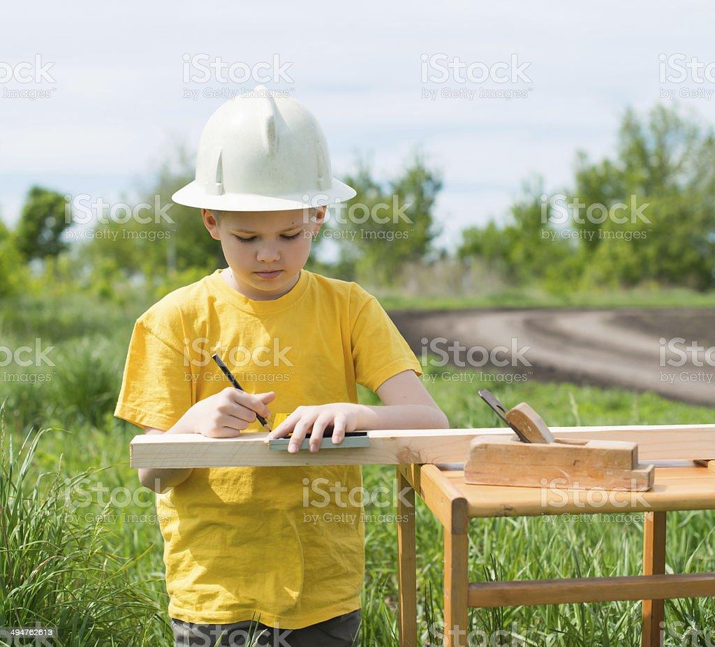 Little carpenter measuring timber. stock photo
