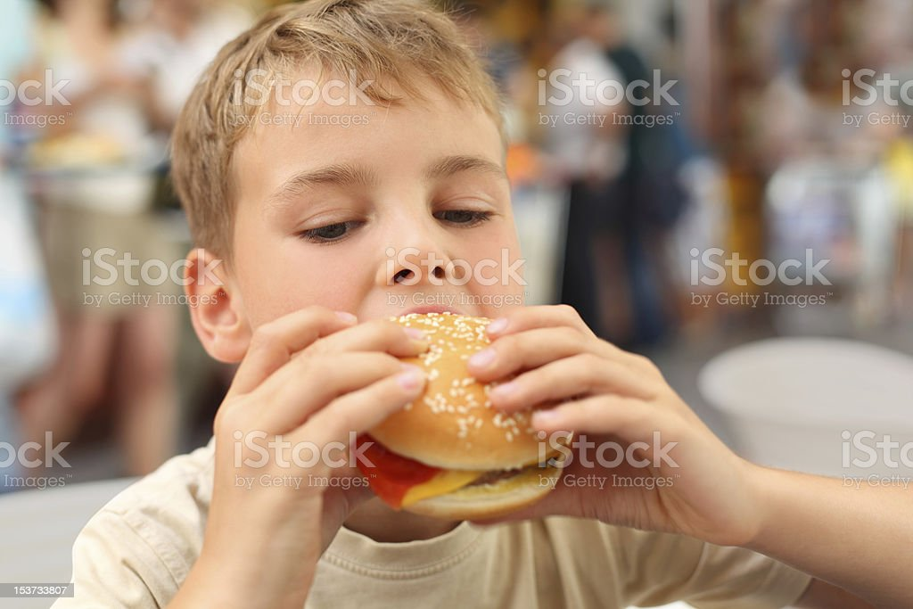 little caucasian boy eating burger, looking down royalty-free stock photo