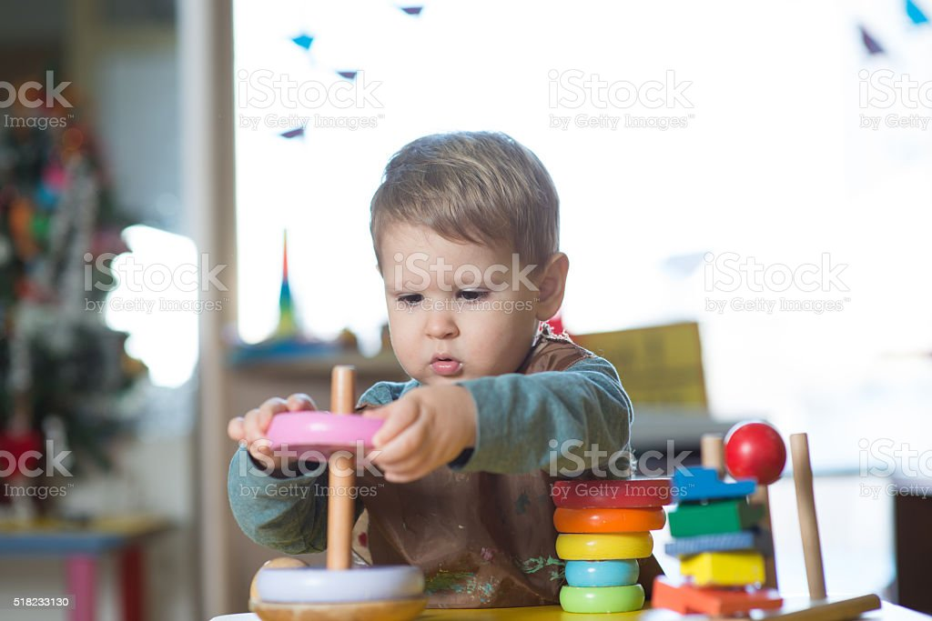 Little caucasian boy playing with Montessori toy in pre-school stock photo
