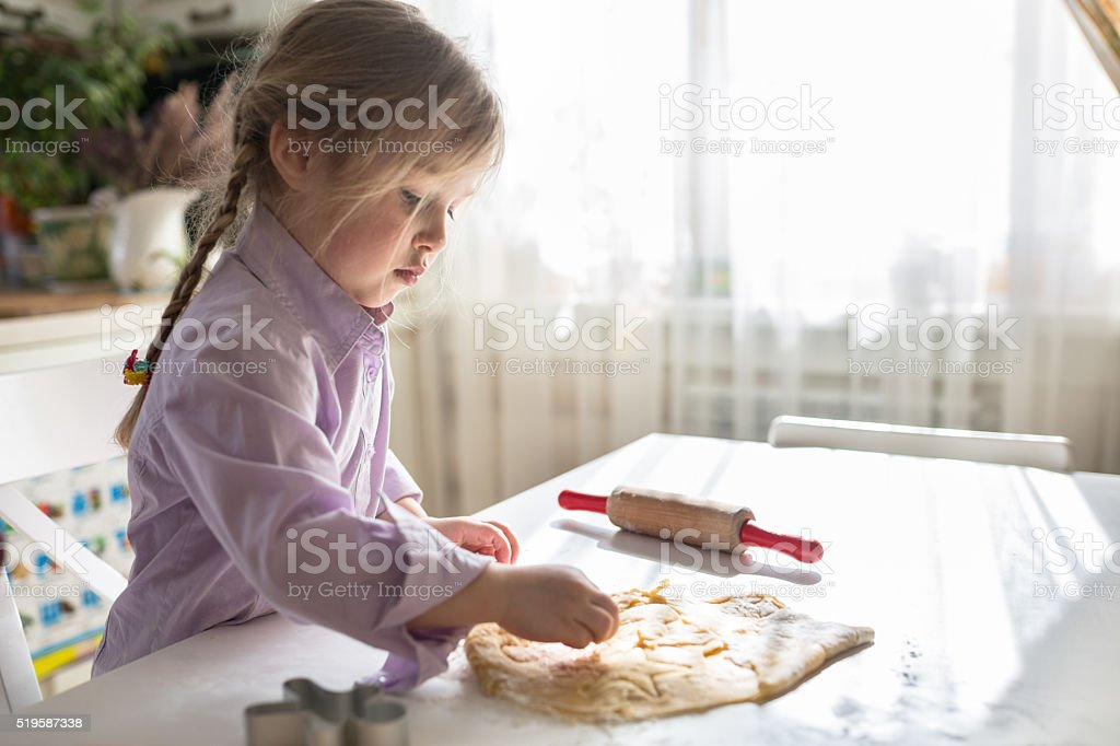 little Caucasian girl with pigtails makes the cookies stock photo