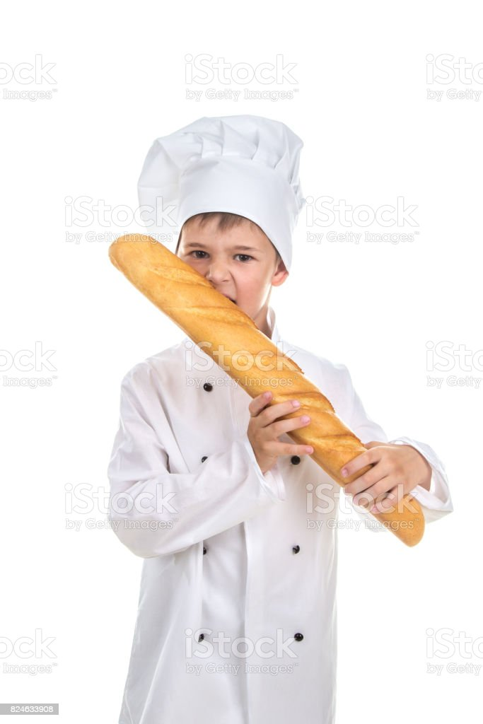 Little chef biting delicious fresh baguette. stock photo