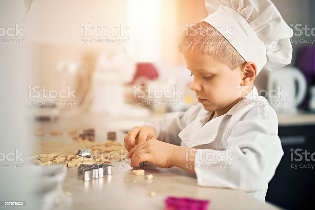 Little chef cutting out cookies in kitchen stock photo