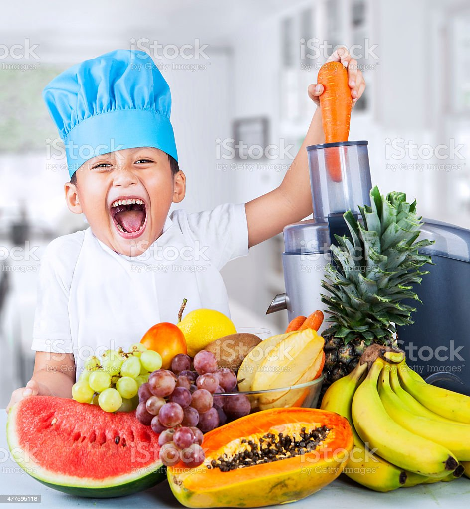 Little chef is making fruit juice stock photo