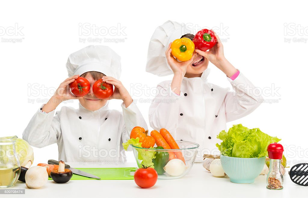 little chefs by table with vegetables stock photo