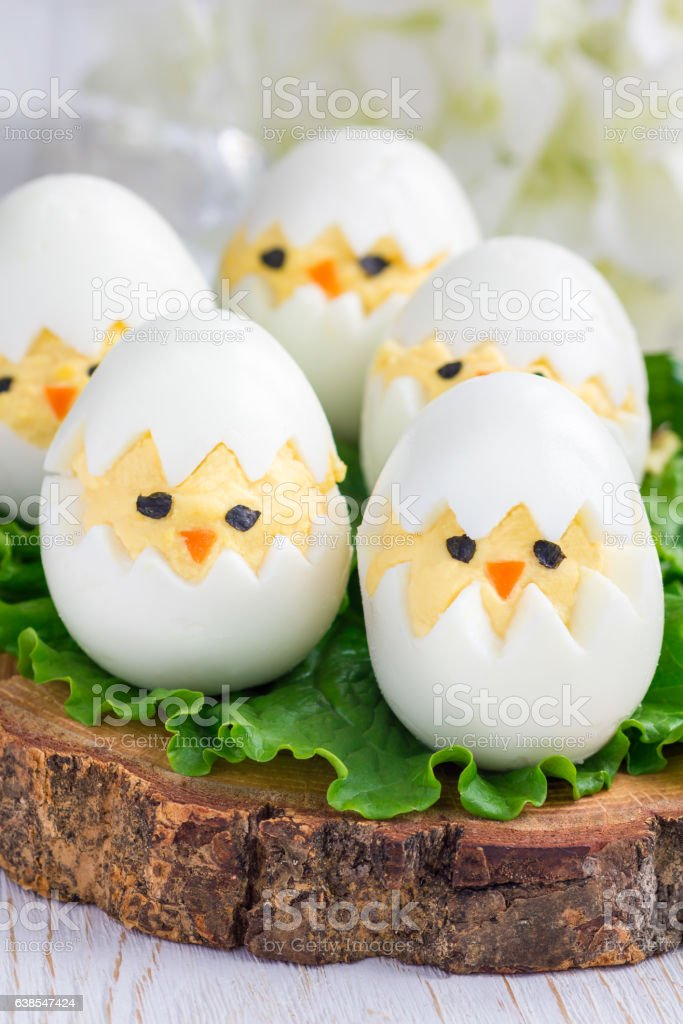 Little chicken in nest, deviled eggs on wooden board, vertical stock photo