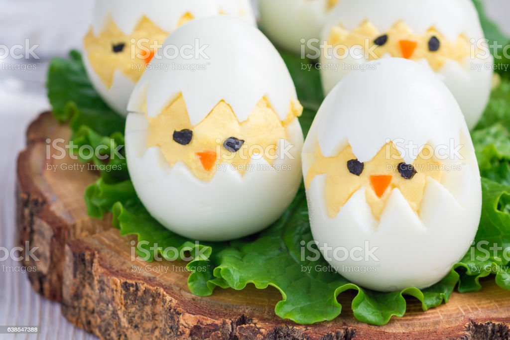 Little chicken in nest, deviled eggs served with salad, horizontal stock photo