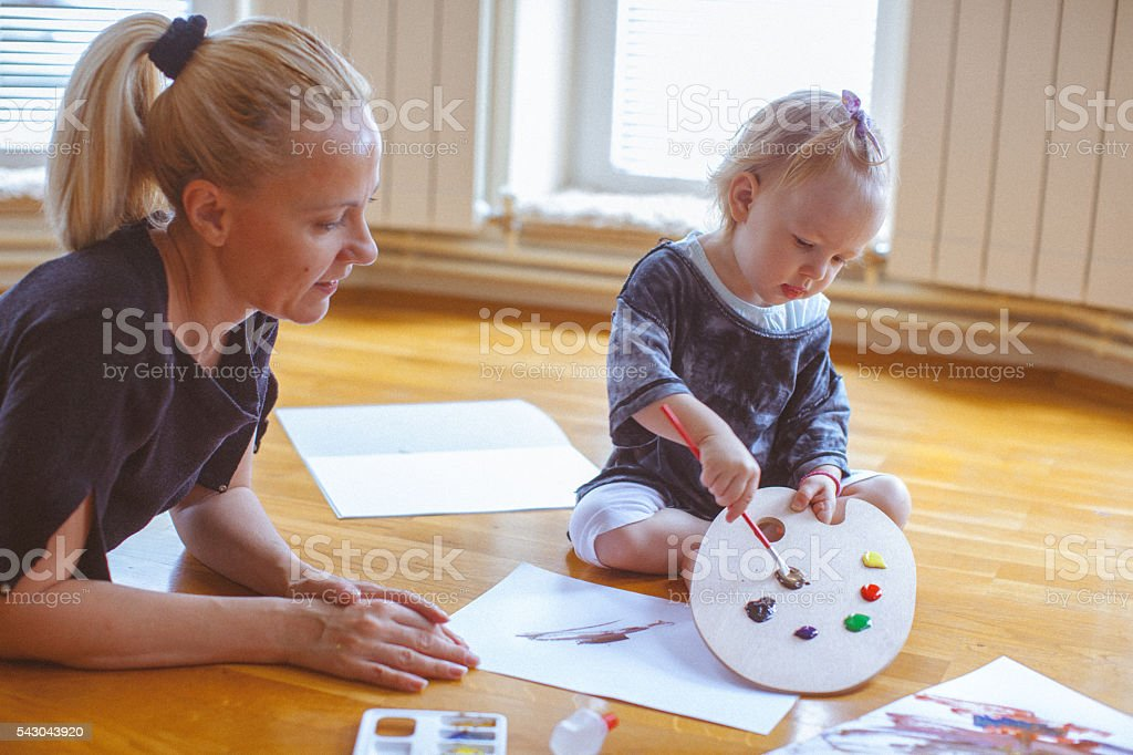 Little child and mother playing with colors and painting together stock photo