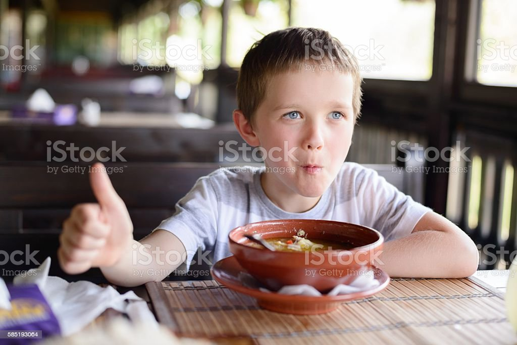 Little child boy enjoying his delicious soup stock photo