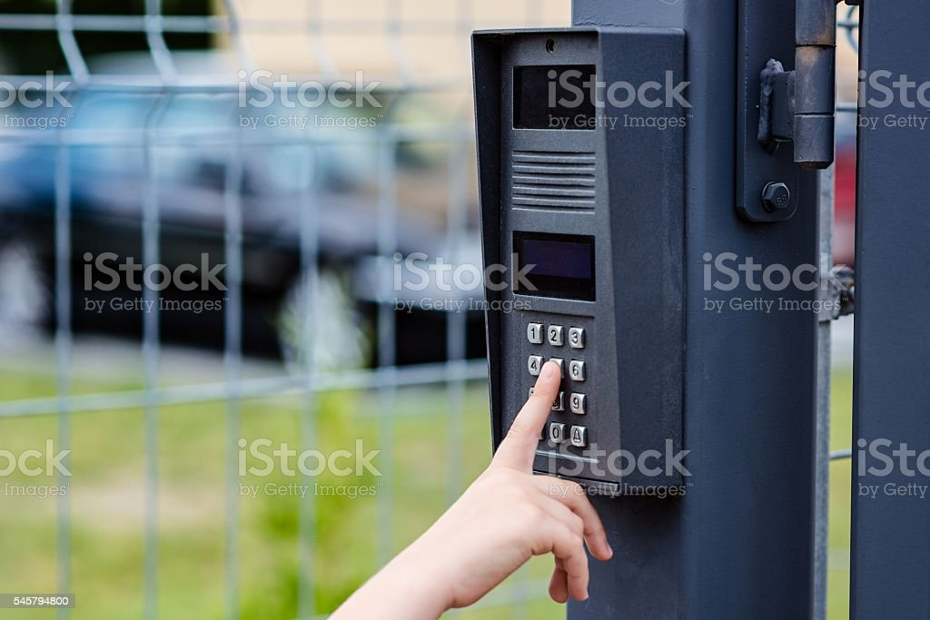 Little child boy pushes a button on the intercom stock photo