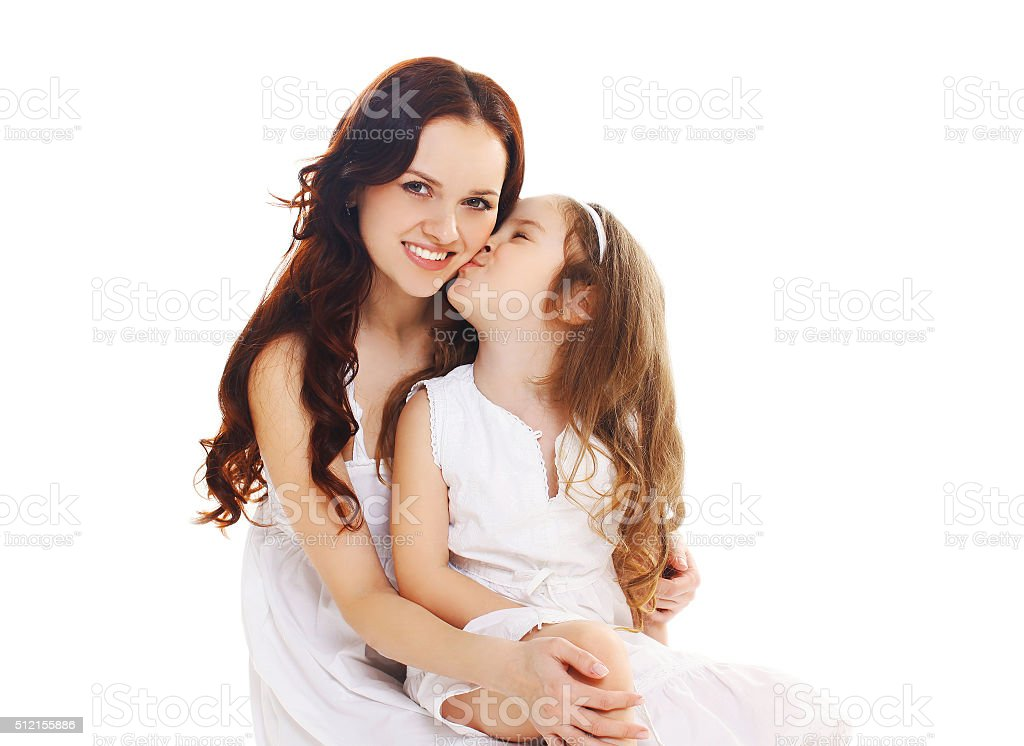 Little child daughter kissing happy mother on white background stock photo