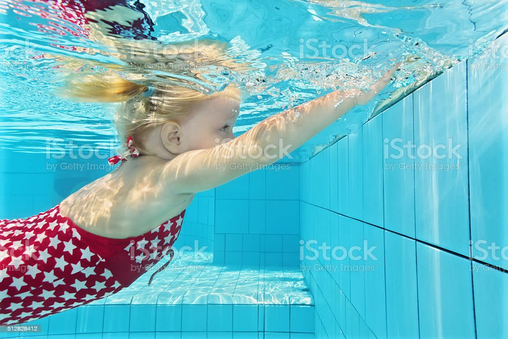 Little child diving underwater in the pool stock photo