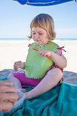 little child eating down umbrella at beach