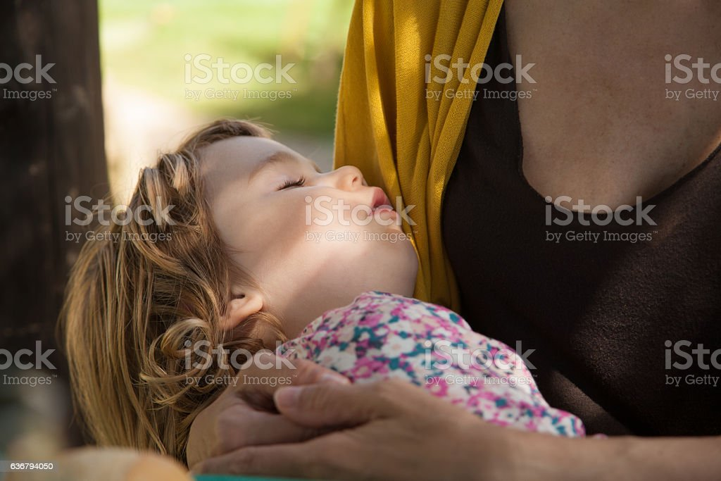 little child face sleeping over mom stock photo