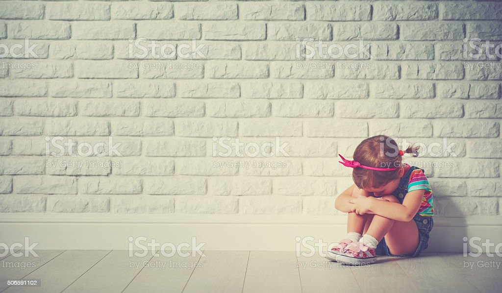 little child girl crying and sad about brick wall stock photo