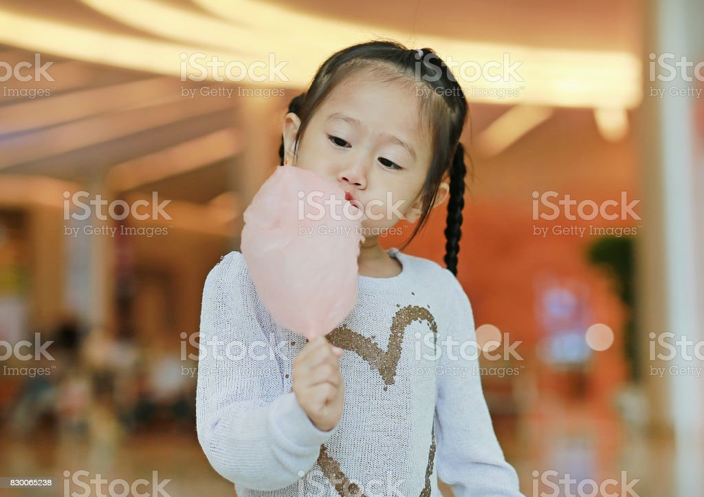 Little child girl eating sweet spongy candy. stock photo